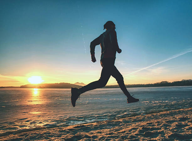Athlete runner running on beach at frozen lake within sunset stock photo