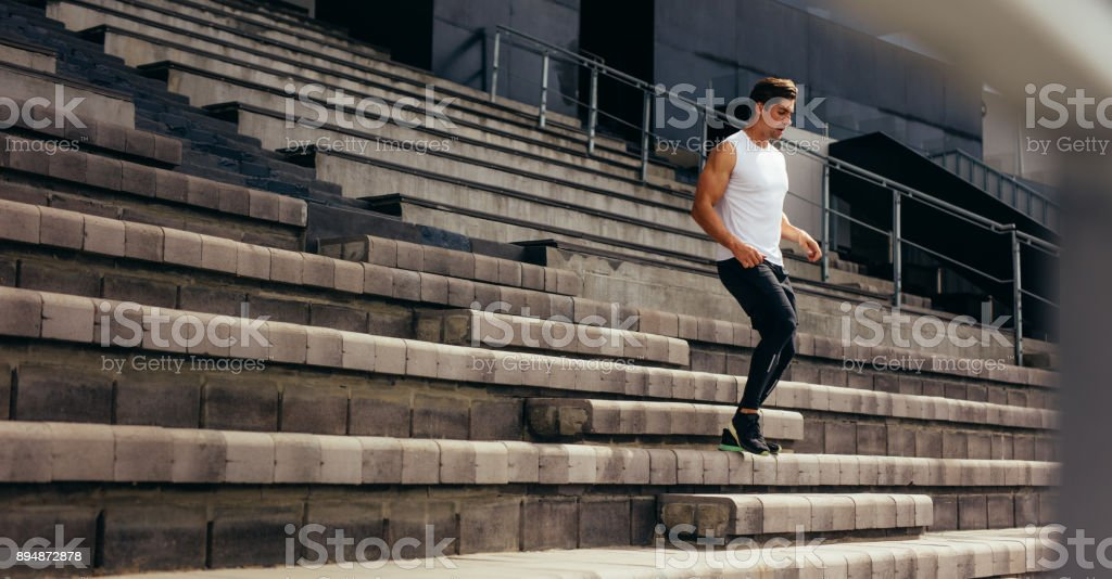 Athlete running down the stairs of a stadium stand stock photo