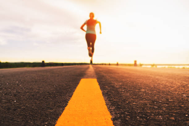 Athlete running on the road trail in sunset training for marathon and fitness. motion blur of woman exercising outdoors stock photo