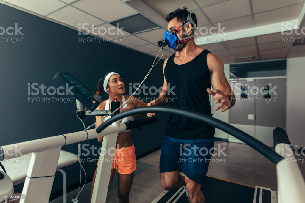 Athlete running on treadmill with female trainer stock photo