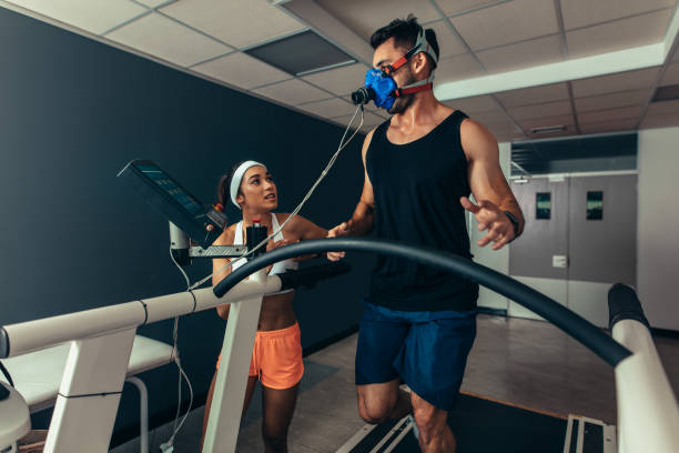 Athlete running on treadmill with female trainer Woman giving instruction to male runner on treadmill in laboratory. Runner with mask on treadmill in laboratory with woman trainer. physiology stock pictures, royalty-free photos & images