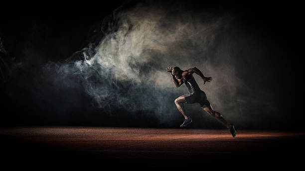 Athlete running Young male athlete running on race track. speed stock pictures, royalty-free photos & images