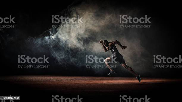 Young male athlete running on race track.