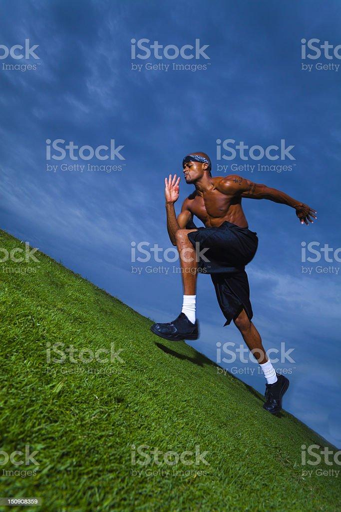 Athlete running up grassy hill royalty-free stock photo