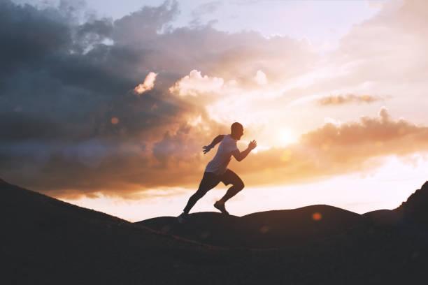 idrottsman går snabbt genom kullarna utomhus i solnedgången. hälsosam livsstilskoncept - jogging hill bildbanksfoton och bilder