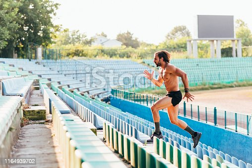 Adult male athlete running at stadium between seats. Shot with Nikon D750 with Nikkor 85 mm 1.8f @ 2.8f