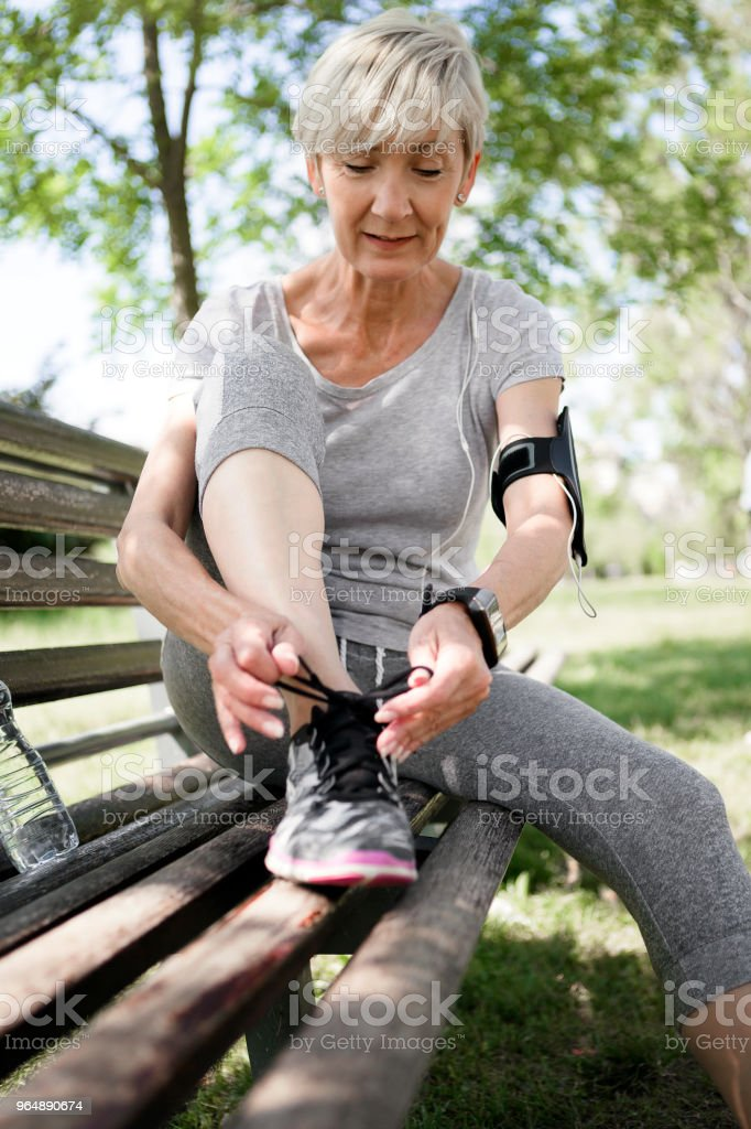 Athlete senior woman tying lace in park getting ready royalty-free stock photo