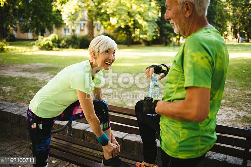 Athlete senior woman tying sport shoe shoelace in the park