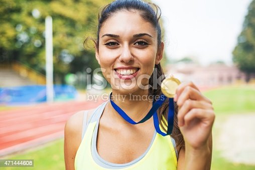 Athlete showing medals. Athletics track in the background