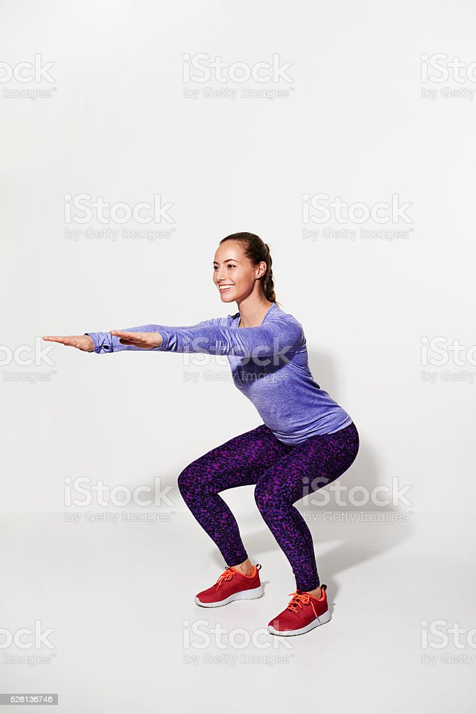 Athlete squatting in studio, smiling stock photo
