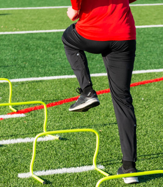 Athlete stepping over yellow mini hurdles stock photo