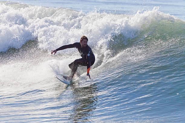 Athlete surfing on Santa Cruz beach in California stock photo