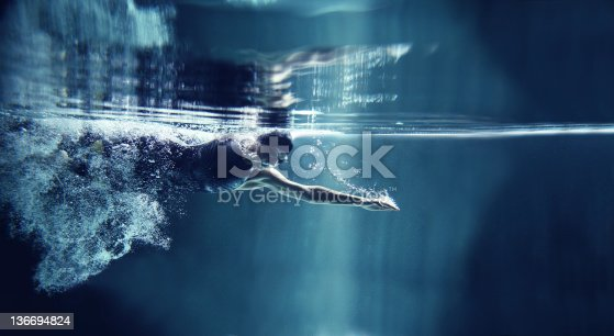 A female athlete is swimming crawl. She is wearing professional, black swim wear, swimming glasses and cap. You can see her torso, head and one hand. She is emerging from air bubbles. She is exhaling air to water and has one arm streatched in front. She is looking down. In the top of image you can see the surface of water and reflection of the scene. The background is dark blue. There are no swimming pool elements. This is a horizontal image.
