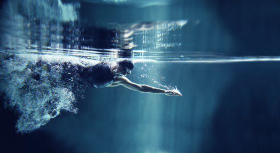 istock Athlete swimming freestyle on blue background, underwater view 136694824