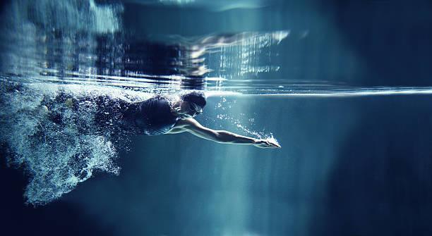 atleta natación freestyle sobre fondo azul, vista submarina - natación fotografías e imágenes de stock