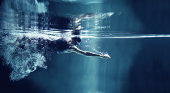 Athlete swimming freestyle on blue background, underwater view