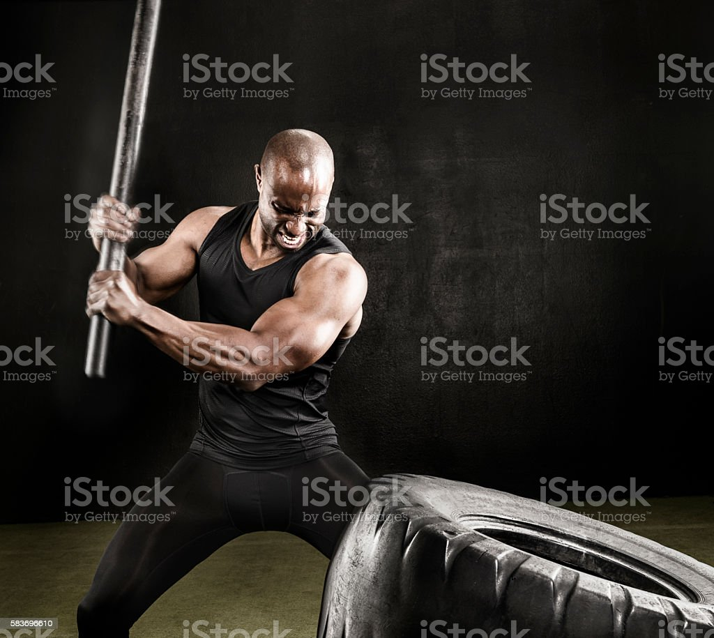 Athlete swinging pipe against tire for workout. stock photo