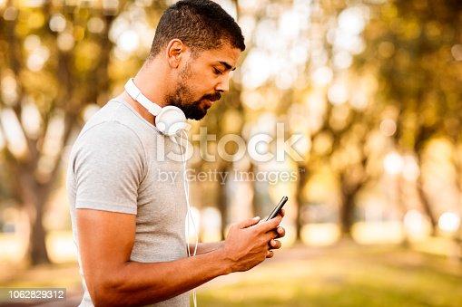 istock Athlete texting on smartphone 1062829312