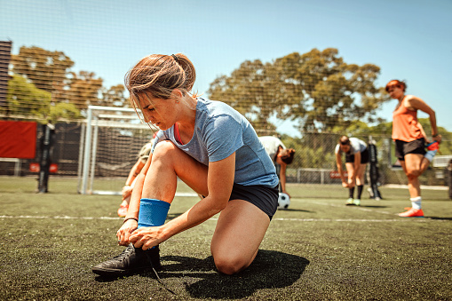 Female soccer players tying shoelace and warming up pre game on soccer field