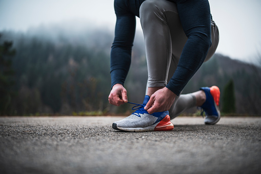 Athlete man with beard kneeling and tying sport shoelaces outdoor, he preparing for run outdoor, autumn weather condition.