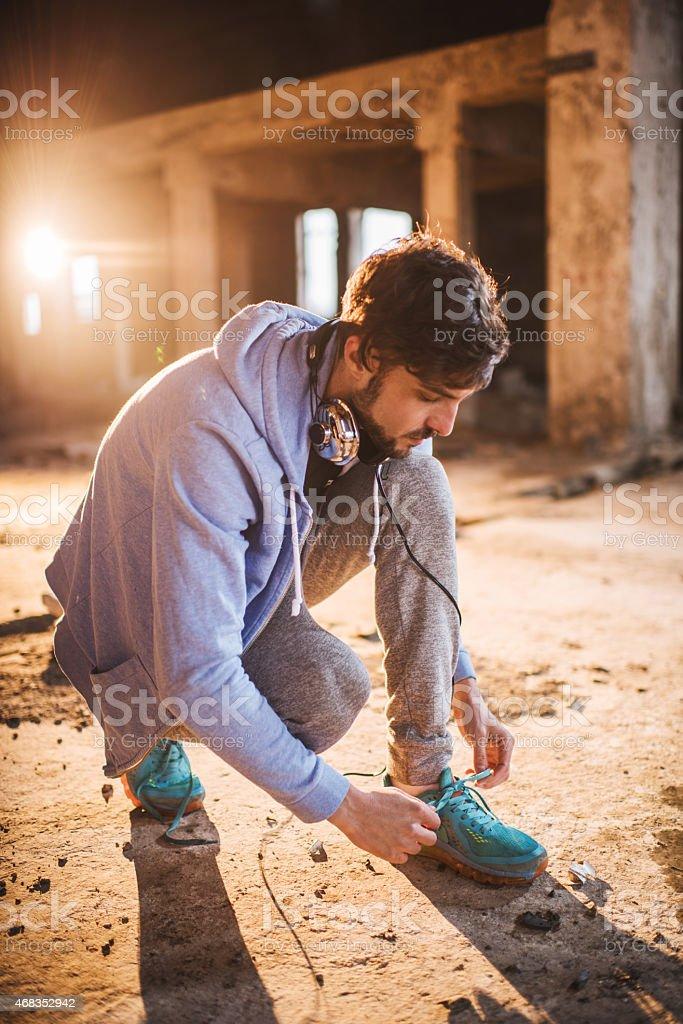 Athlete tying shoelaces and preparing for exercising. royalty-free stock photo