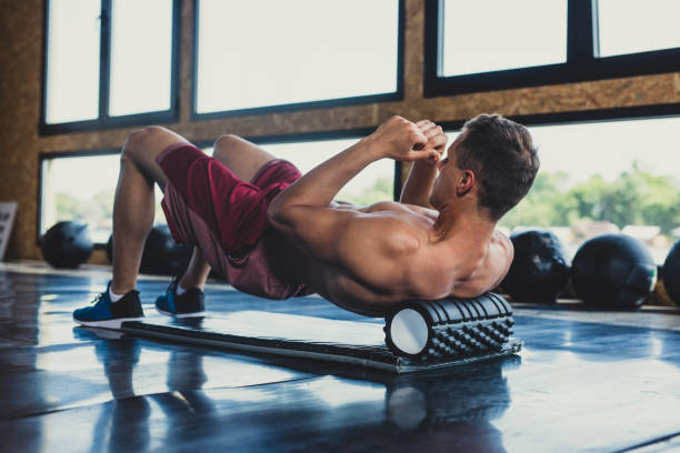 Athlete Using a Foam Roller Handsome young muscular Caucasian man massaging his upper back with a foam roller in an indoor gym. build muscles stock pictures, royalty-free photos & images