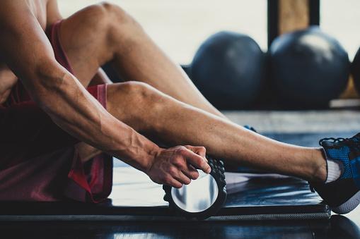 Muscular Caucasian man massaging his calves with a foam roller in an indoor gym.