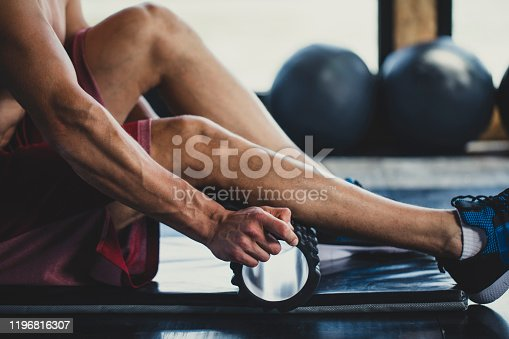 Muscular Caucasian man massaging his calves with a foam roller in an indoor gym.
