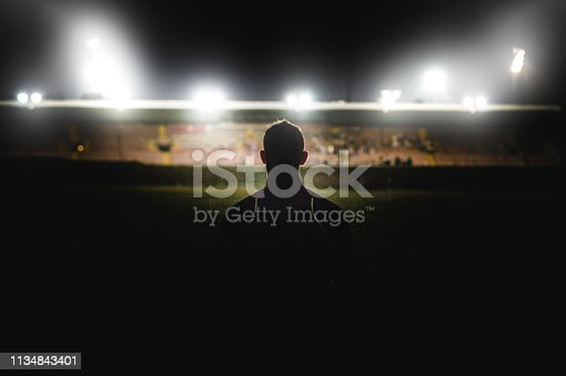 A young muscular Caucasian male walking in the rain at night in front of a stadium with stadium floodlights spotlights towards the competition near Cape Town South Africa