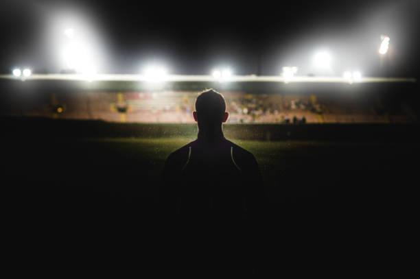 athlet zu fuß in richtung stadionsilhouette - gegenlicht stock-fotos und bilder