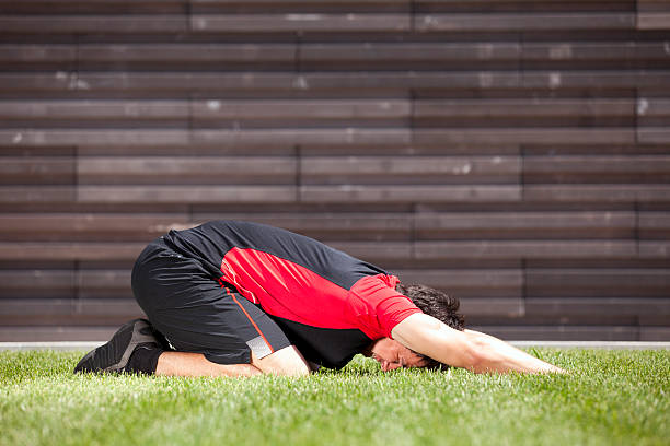 Athlete warming and stretching Athlete at the park warming and stretching touching toes stock pictures, royalty-free photos & images