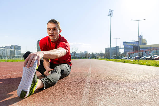 Athlete warming and stretching Young man working out outside touching toes stock pictures, royalty-free photos & images