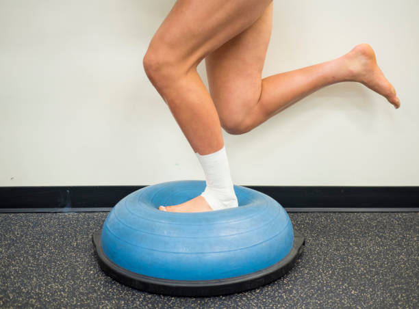 Athlete with a sprained ankle doing strengthening and balance exercises on a bosu ball stock photo