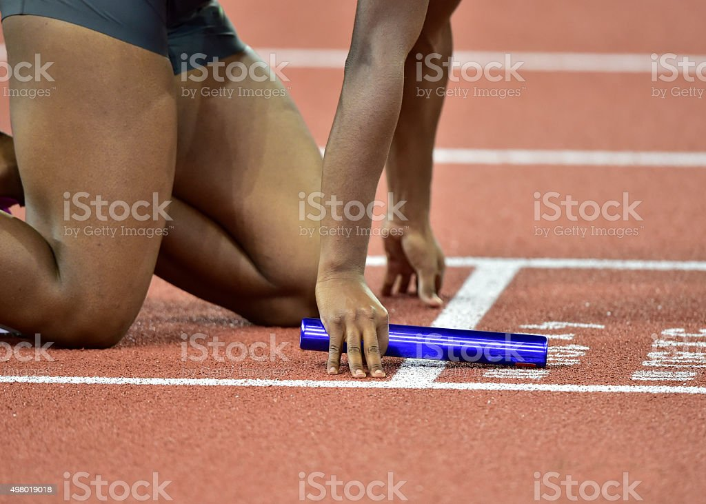 athlete with baton concentrating before the start of relay race stock photo