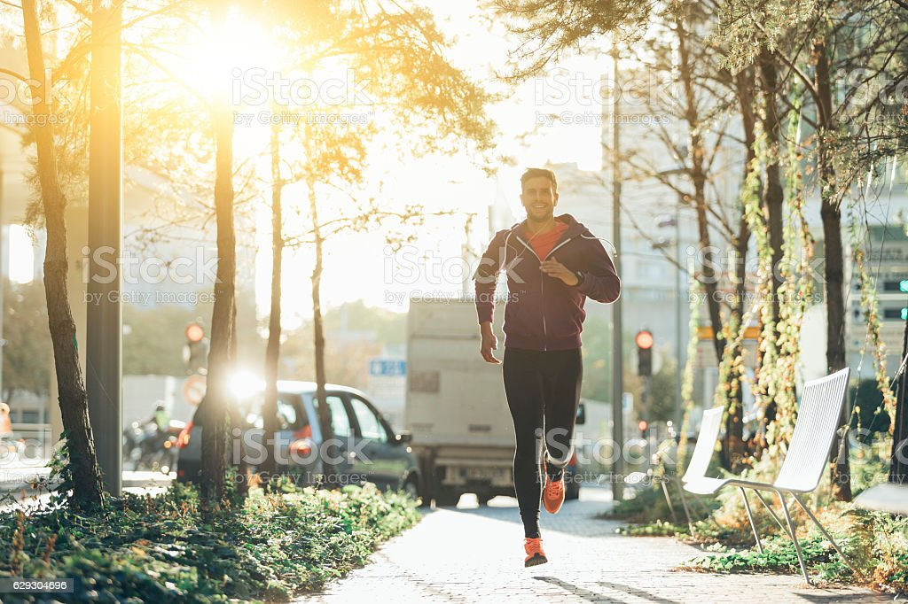 athlete with earphones running in the city stock photo