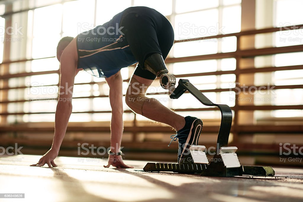 Athlete with prosthetic leg at running track stock photo