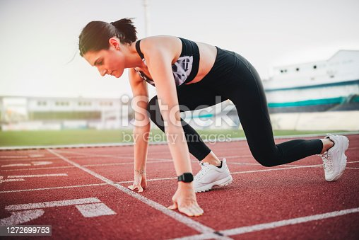 istock Athlete woman at starting line ready to run 1272699753