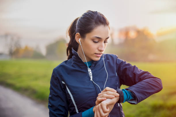 """Athlete woman check smartwatch Young athlete listening to music during workout at park and adjusting smart watch. Young latin woman setting smartwatch before jogging in winter or autumn.""""r woman taking pulse stock pictures, royalty-free photos & images"""