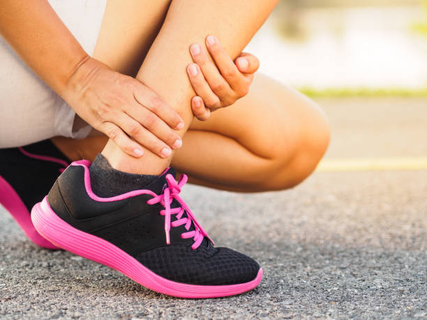 athlete woman has ankle injury, sprained leg during running training. sport concept. - slogatura foto e immagini stock