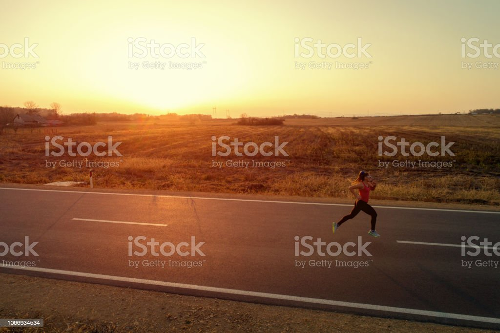 Young woman jogging over empty road at sunset. She is marathon runner