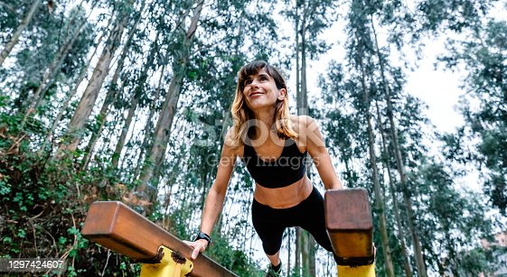 Happy athlete woman training on parallel bars in a park