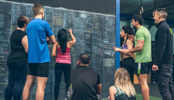 Sportlerin schreibt Ergebnisse auf der Gym-Tafel auf – Foto