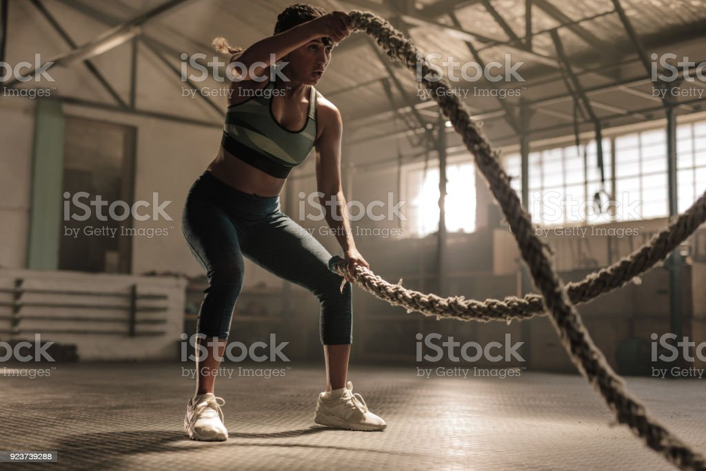 Athlete working out with battle ropes at cross gym stock photo