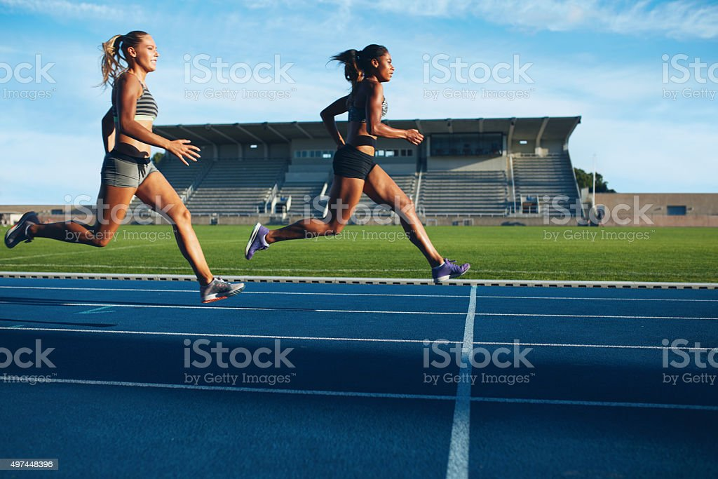 Athletes arrives at finish line on racetrack stock photo