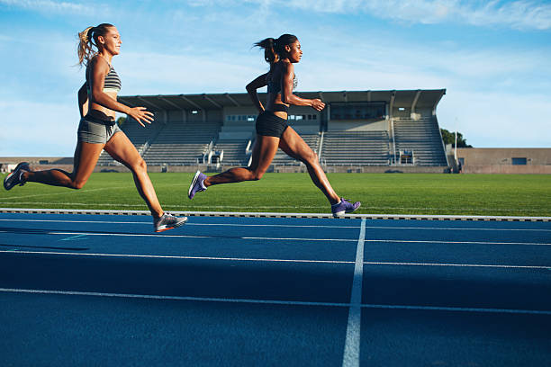 athletes arrives at finish line on racetrack - finishing stock photos and pictures