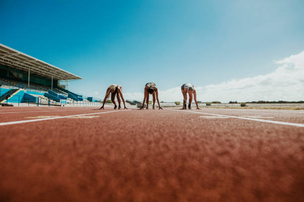 Athletes at starting line on running track Three young athletes at starting position ready to start a race. Sports women ready for race on racetrack. women's track stock pictures, royalty-free photos & images