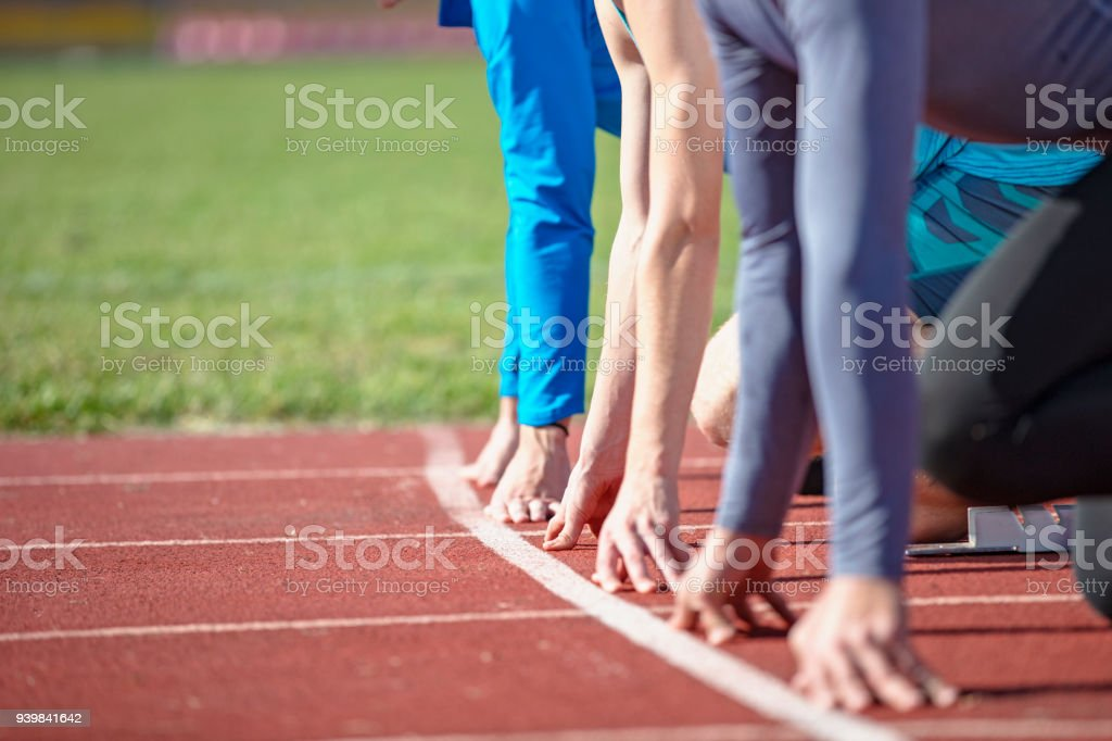 Athletes at the sprint start line in track and field stock photo
