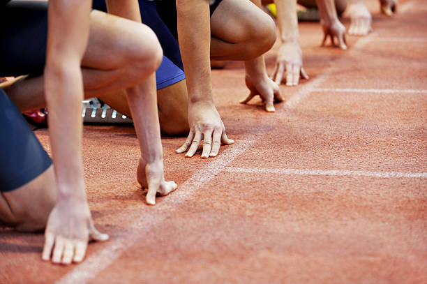 Athletes at the sprint start line Athletes at the sprint start line in track and field track starting block stock pictures, royalty-free photos & images