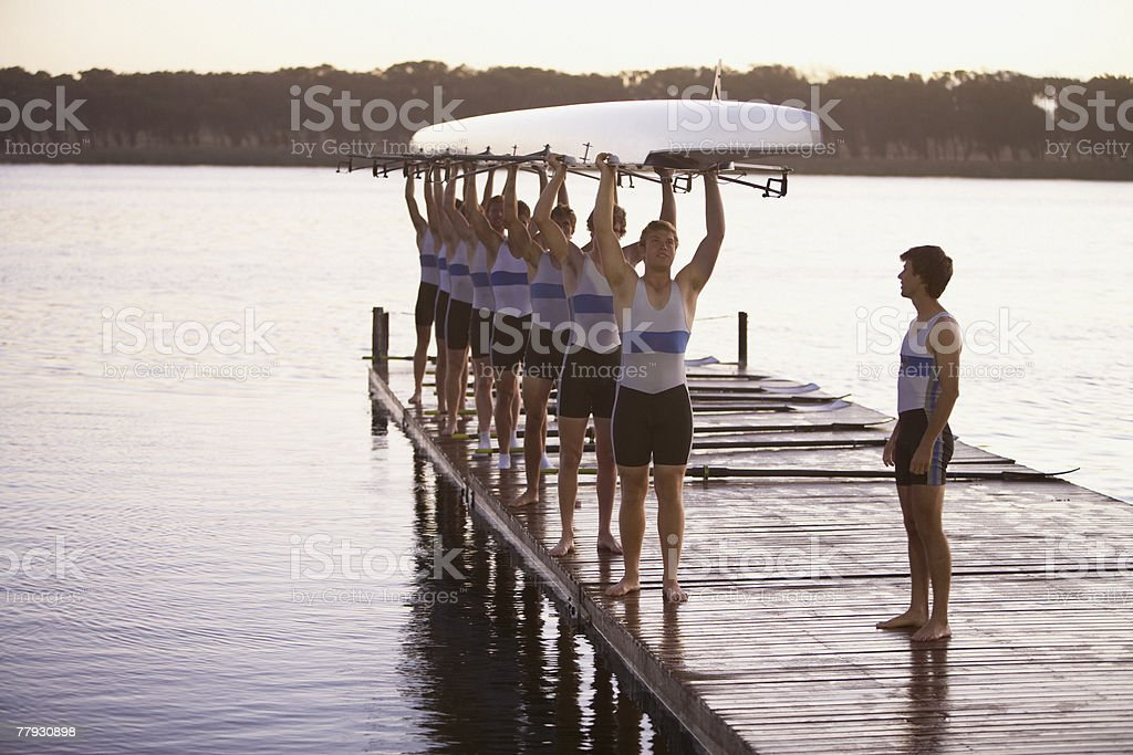 Athletes carrying a crew row boat over heads royalty-free stock photo