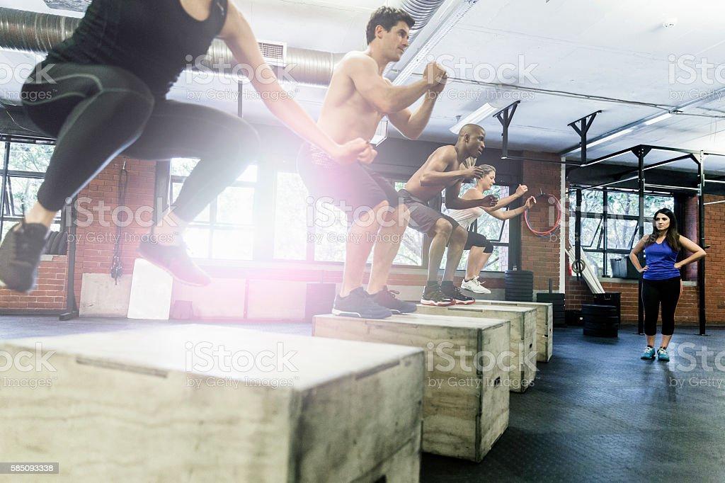 Athletes doing box jumping at gym royalty-free stock photo